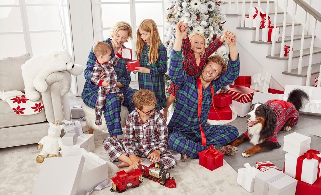family wearing matching pajamas and opening presents