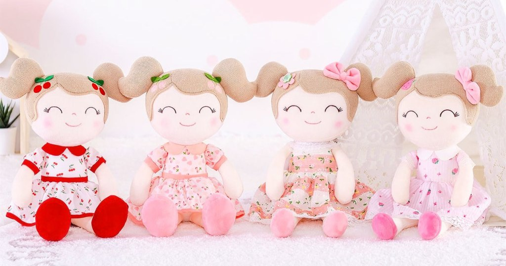 four girl plush dolls with brown pigtail hair and wearing pink printed dresses