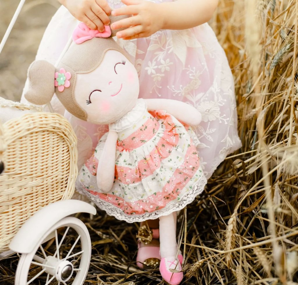 toddler girl in a pink lace dress holding a ballerina plush doll in her hand