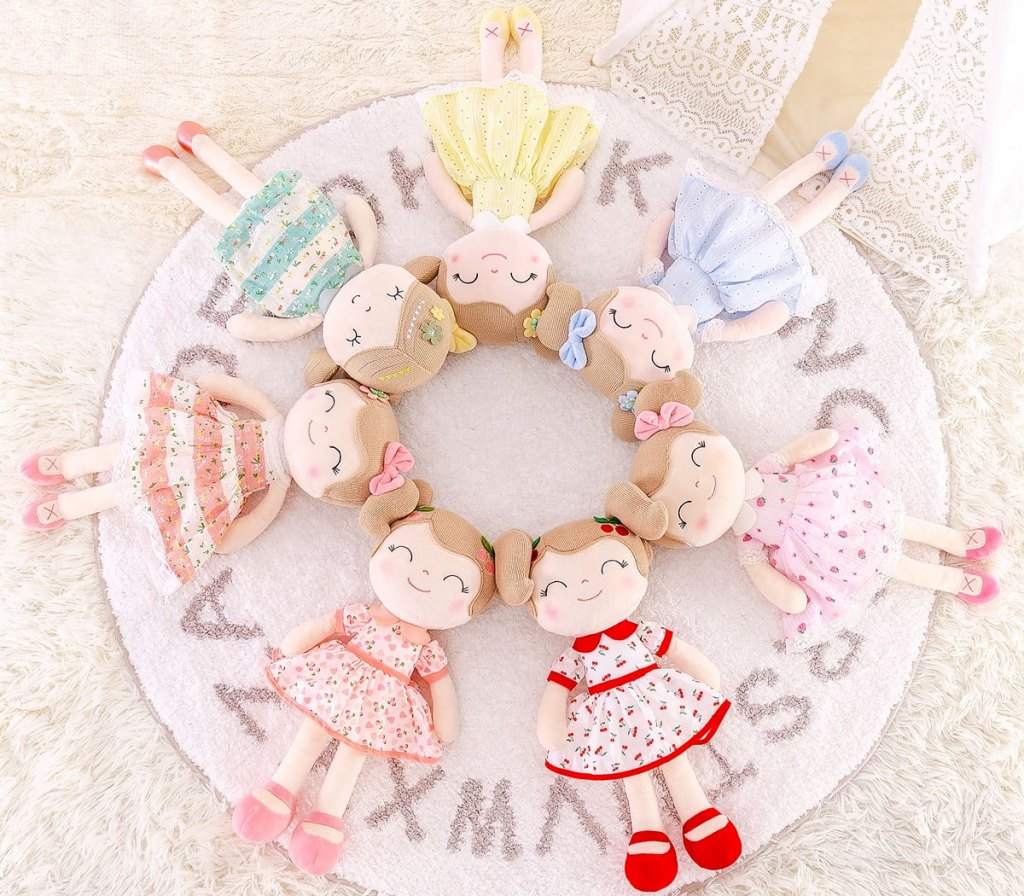 plush girl dolls in printed dresses arranged in a circle on a white circular alphabet rug