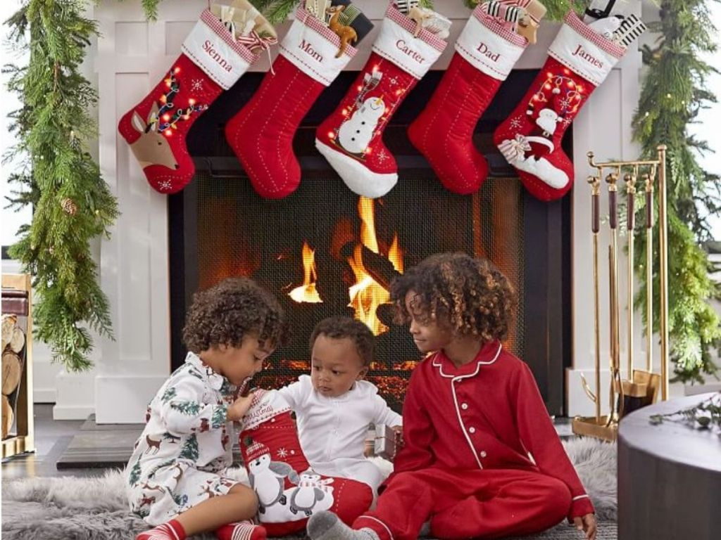 mantel with Christmas Stockings hanging from it and children sitting in front of it