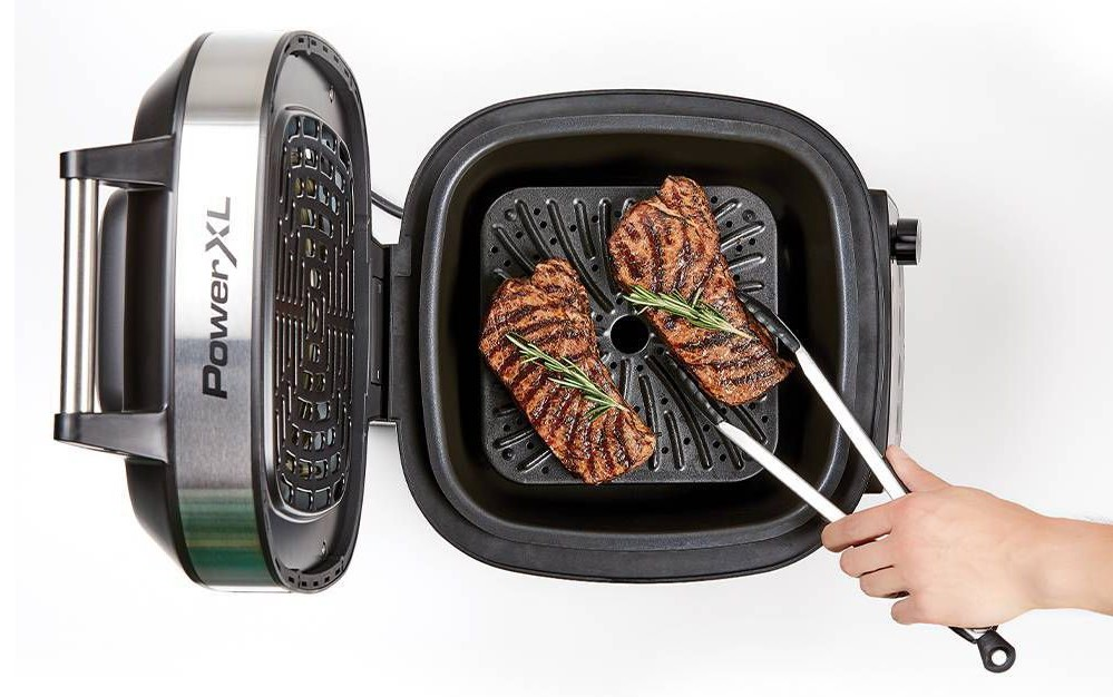 person taking food out of a grill
