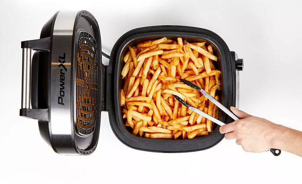 hand taking french fries out of an air fryer