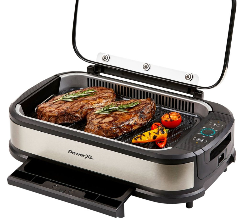 black and stainless steel indoor grill with two steaks and veggies on grilling surface