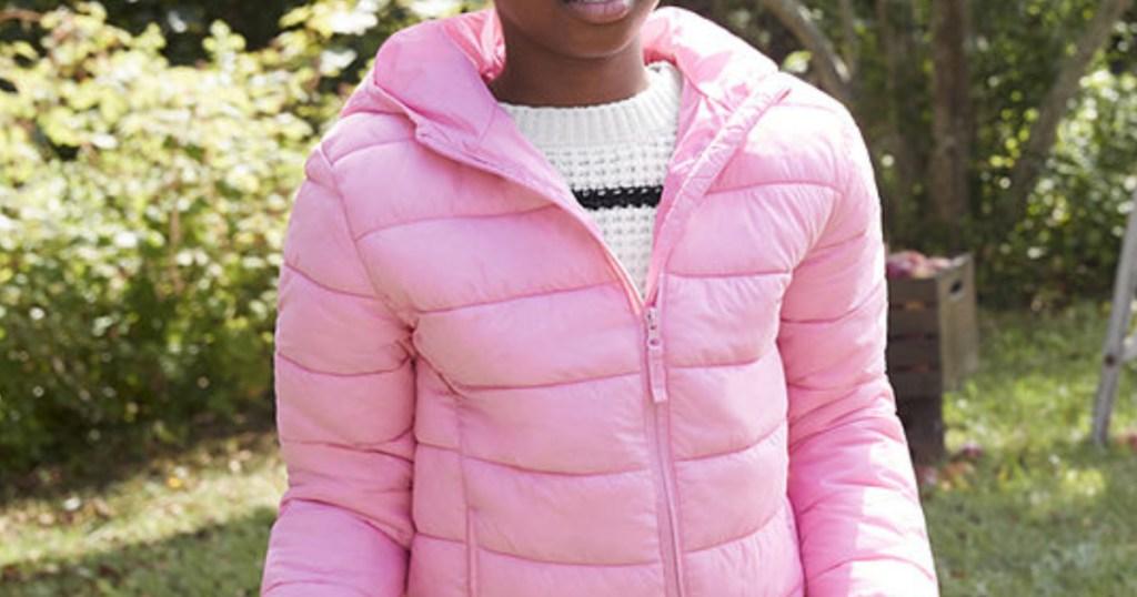 little girl wearing a light pink puffer jacket outside
