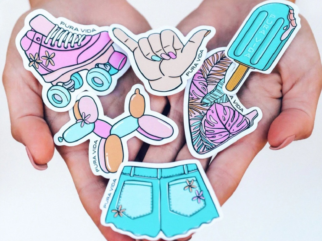 hand holding multiple pura vida stickers outside
