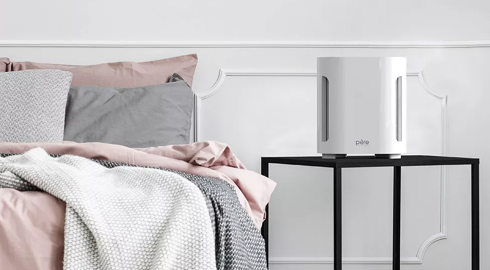 bed with a side table and air purifier
