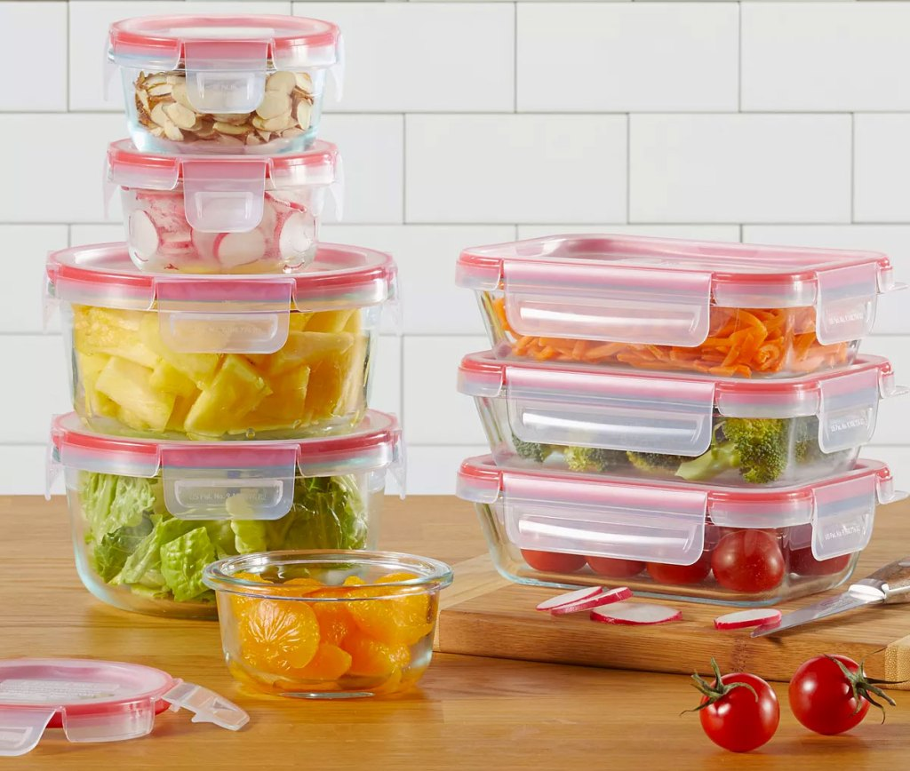 pyrex glass food storage set with red plastic lids with snap-on sides stacked with foods on a wood cutting board