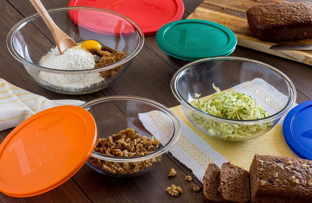 pyrex glass mixing bowl set with colorful lids on a table with zucchini bread ingredients inside