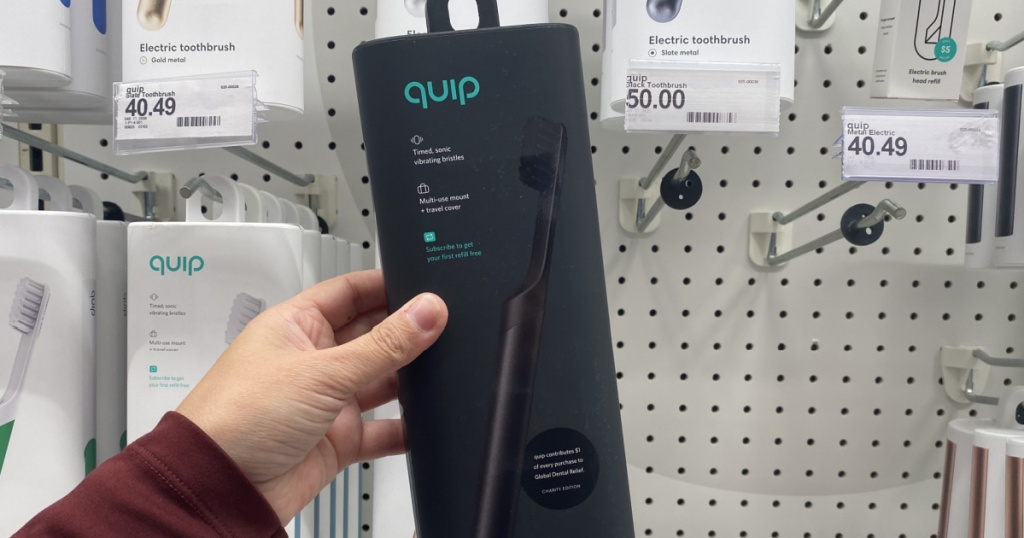 hand holding an all black quip toothbrush at target