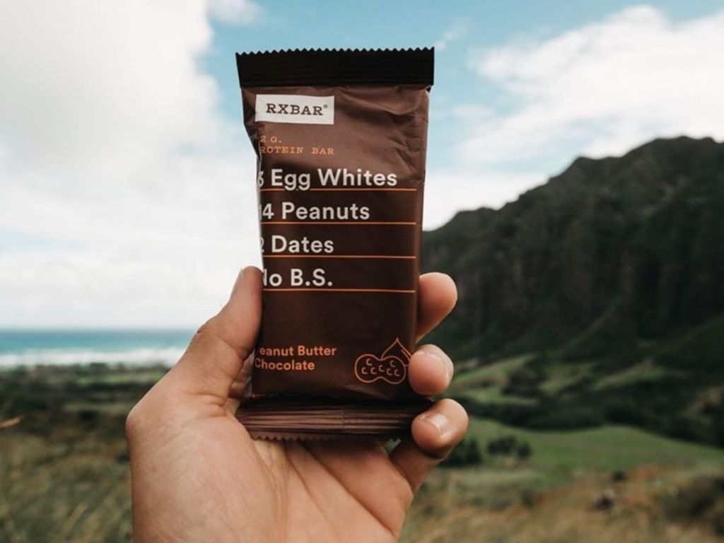hand holding RXBAR peanut butter chocolate bar with nature background