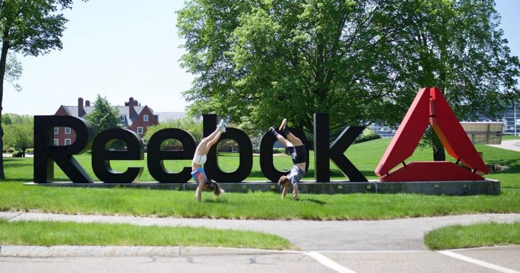 2 people doing handstands in front of the Reebok sign
