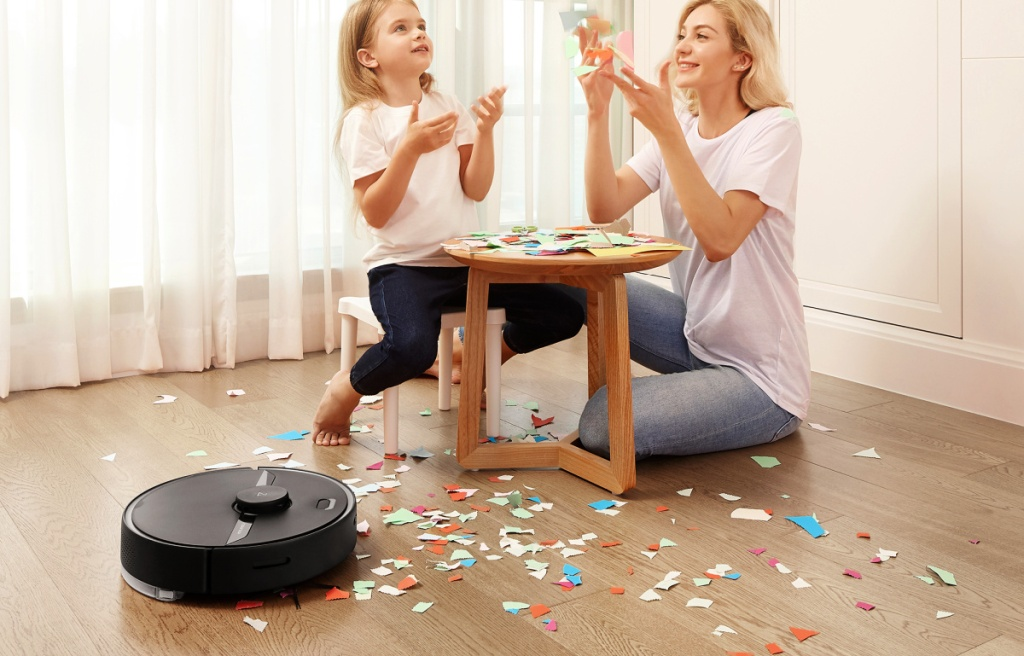 Roborock S6 Robot Vacuum and Mop cleaning up confetti from floor with mother and daughter