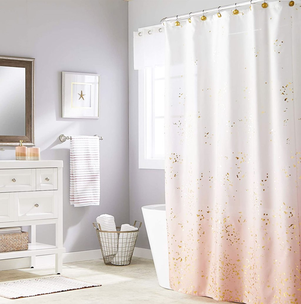 white and pink ombre shower curtain with gold splatter on it hanging in a bathroom