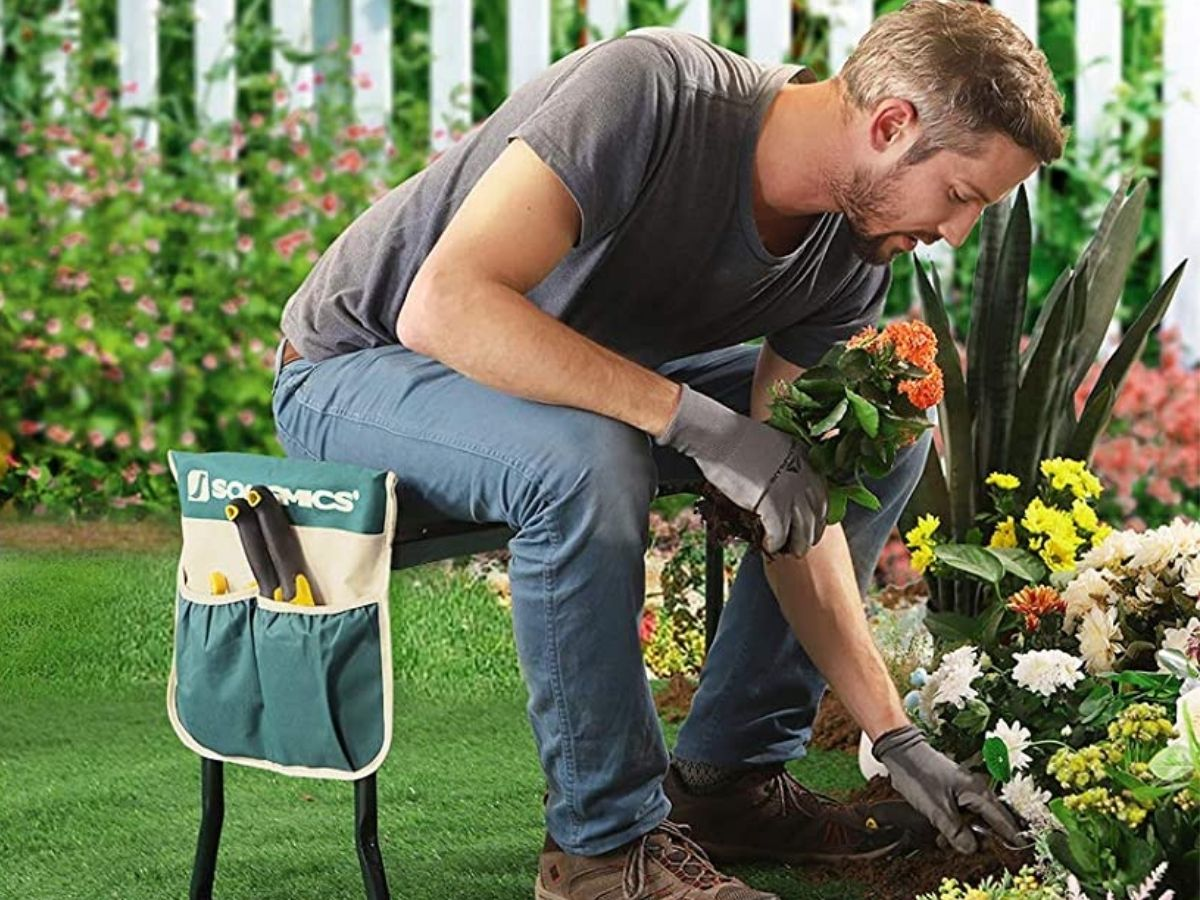 man sitting on bench while planting flowers