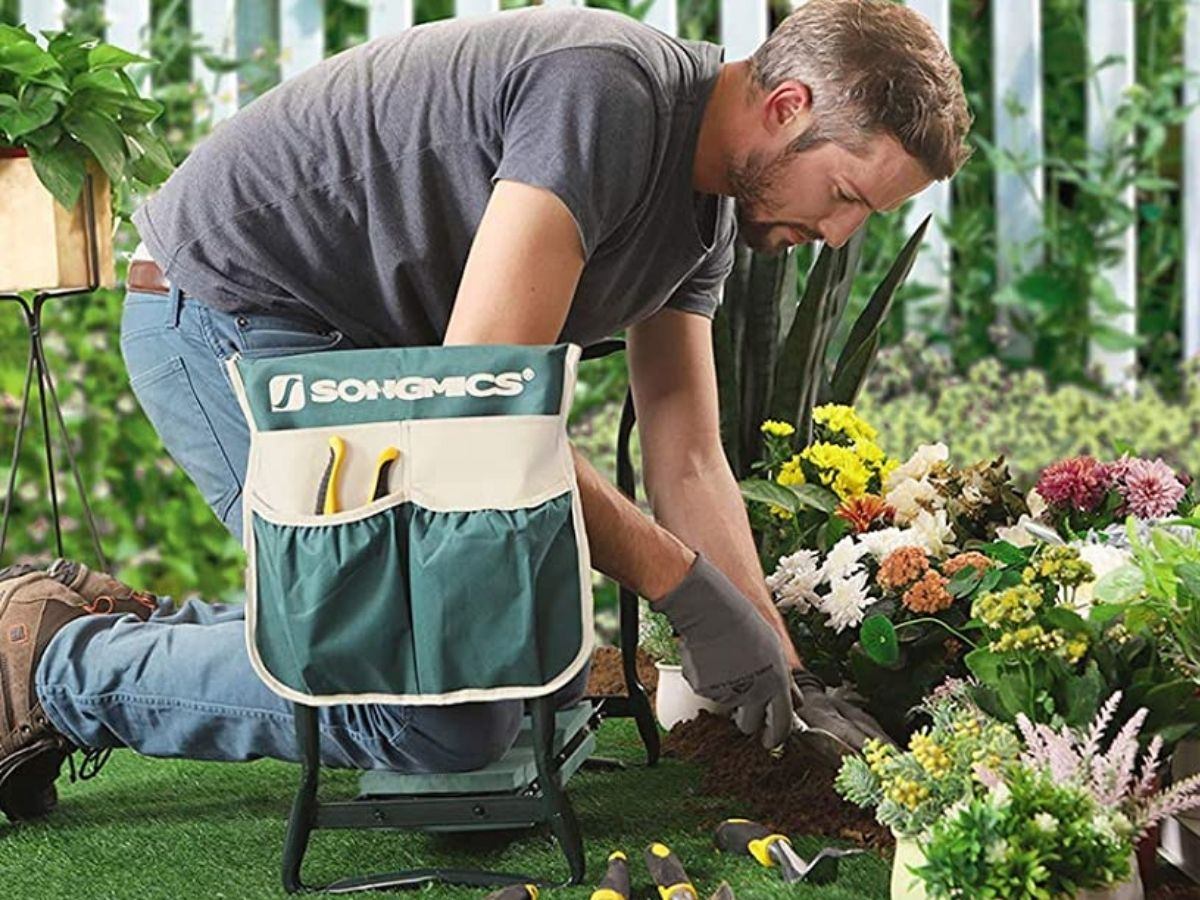 man using bench for knee pad while planting flowers