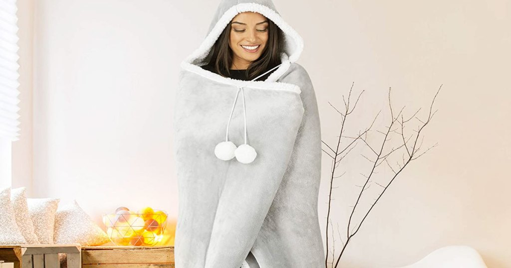 woman wrapped up in a grey sherpa hooded blanket with two white pompoms
