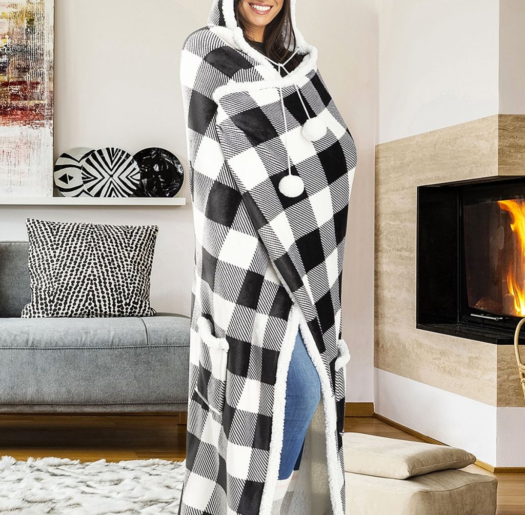 woman wrapped in a black and white buffalo plaid patterned blanket with a hood
