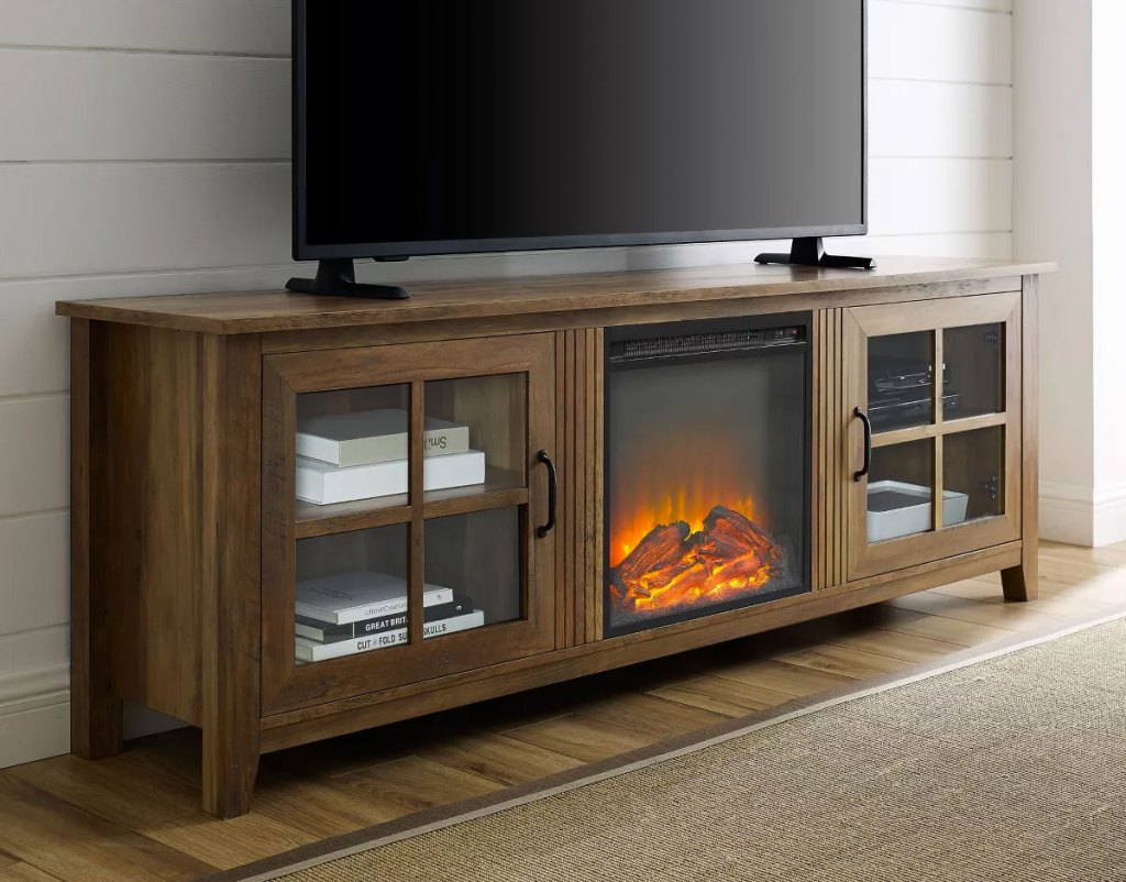 brown wood tv stand with two glass doors and electric fireplace in center