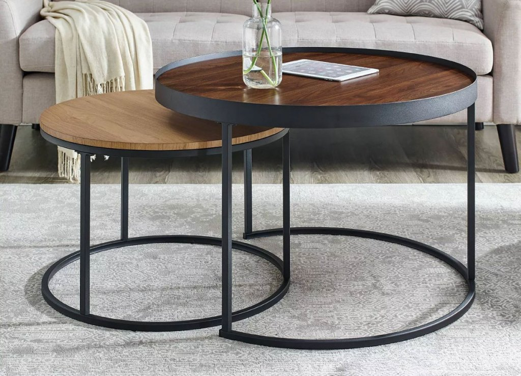 set of two round wood topped coffee tables that nest into each other