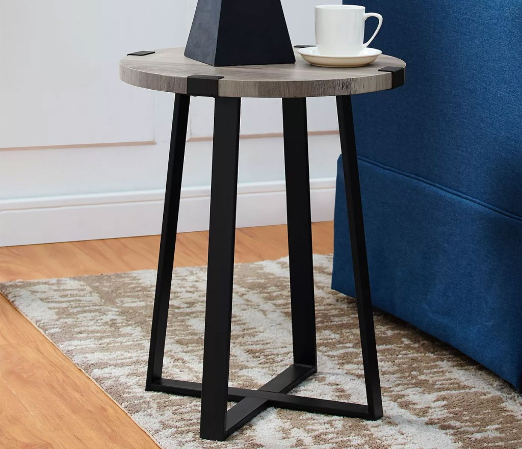 round wood top side table with black metal industrial legs next to blue couch