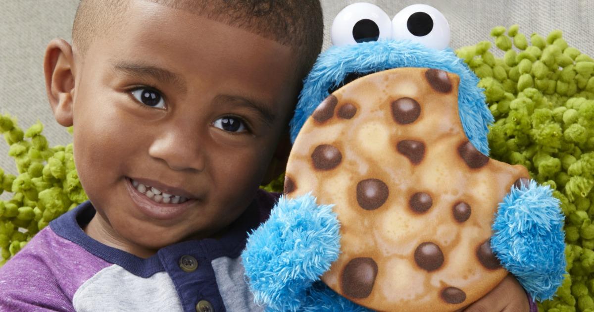little boy holding Sesame Street Peekaboo Cookie Monster plush toy
