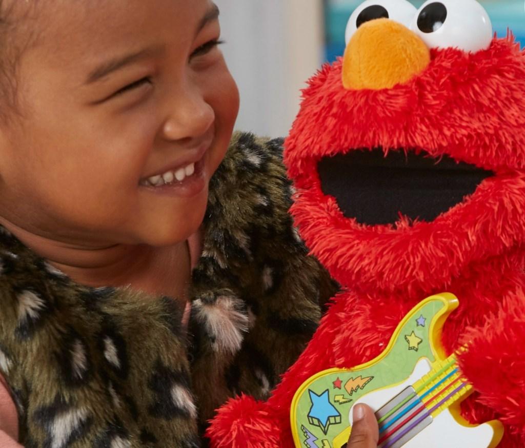 toddler holding Sesame Street Rock and Rhyme Elmo