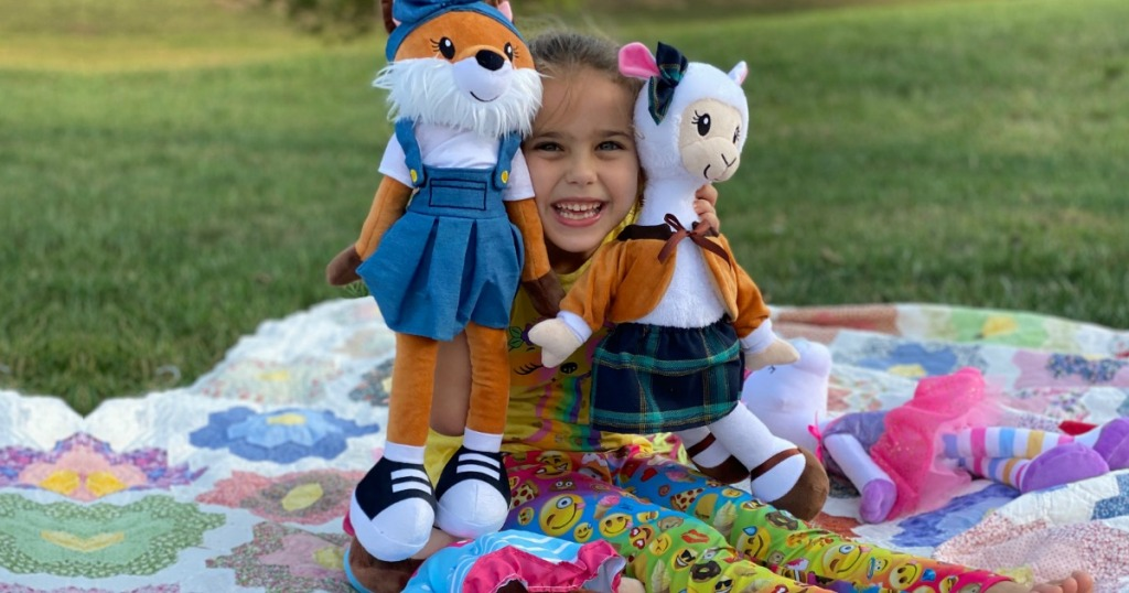 little girl sitting outside with Sharewood Friends plush dolls