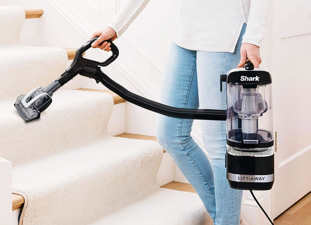 woman holding a shark liftaway vacuum in one hand and using floor attachment in other hand to clean stairs