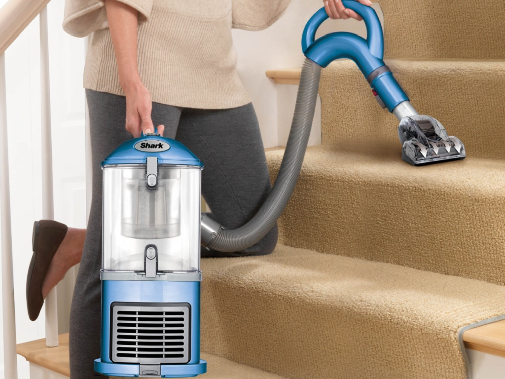 woman vacuuming carpet on staircase with blue vacuum