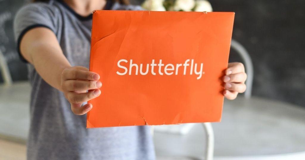 child hand holding shutterfly envelope