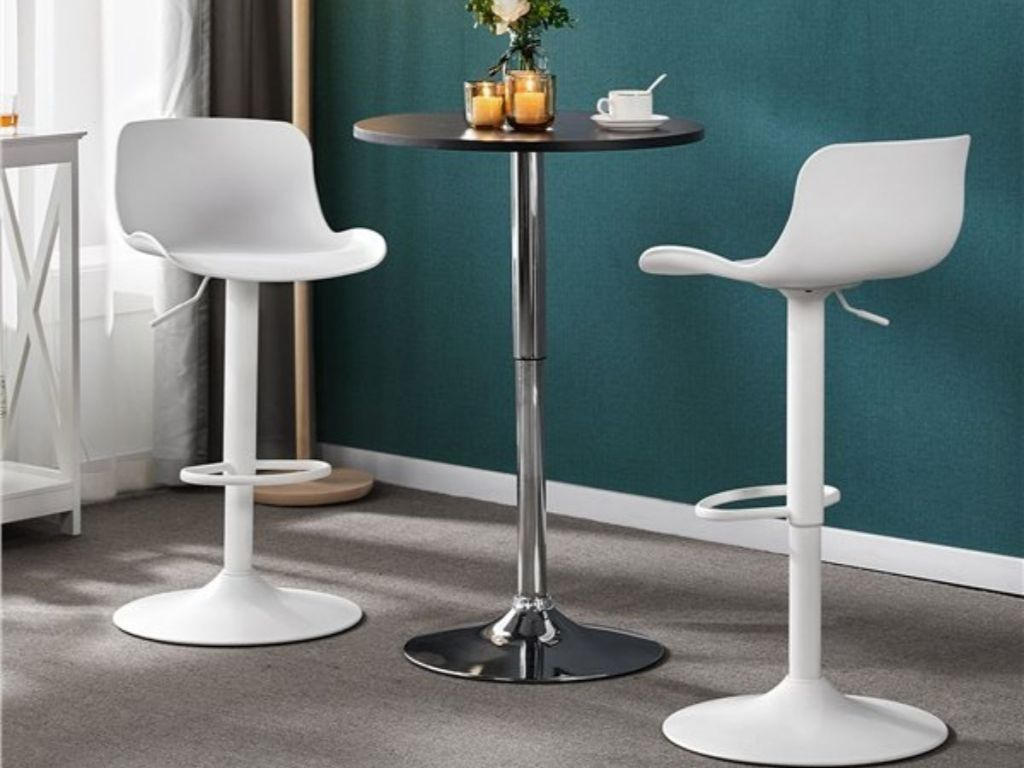 two adjustable bar stools next to a small table