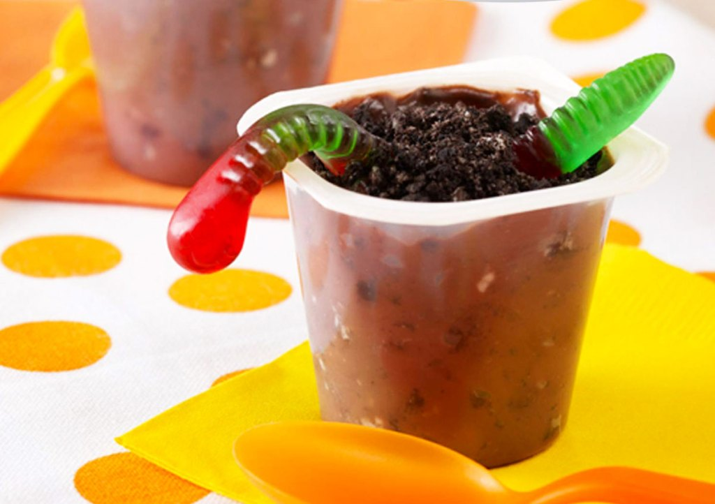 snack pack chocolate pudding cup with red and green gummy worm and oreo dirt inside of it
