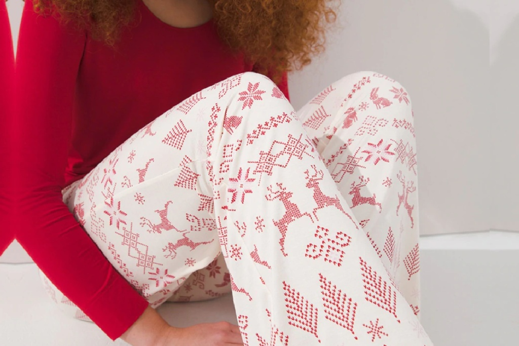 woman sitting on a floor wearing red and white soma pajamas