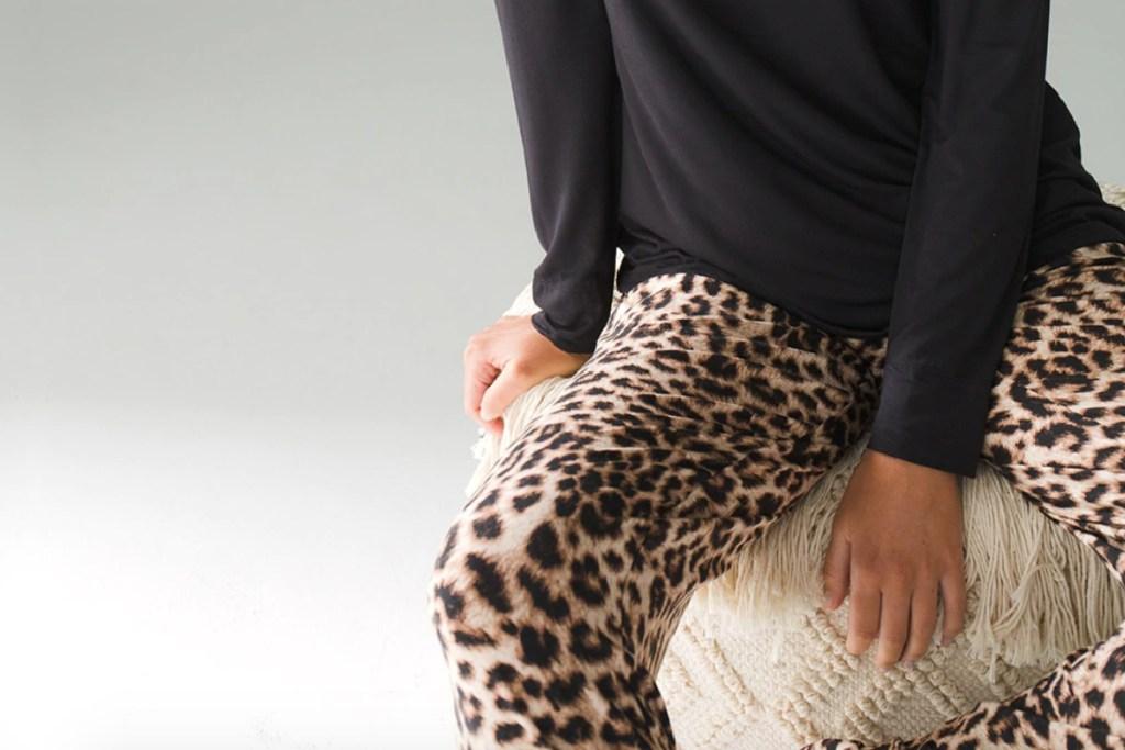 woman sitting wearing cheetah pajamas