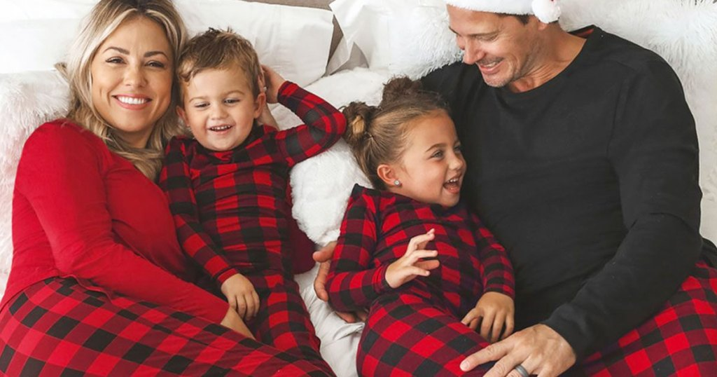 family of four laying in bed wearing matching red and black buffalo plaid pajamas
