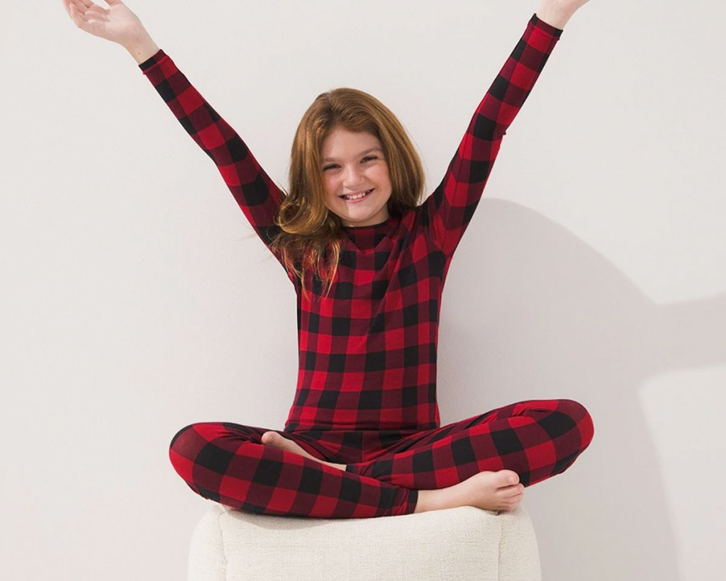 girl sitting on an ottoman with hands in the air wearing a set of red and black buffalo plaid pajamas