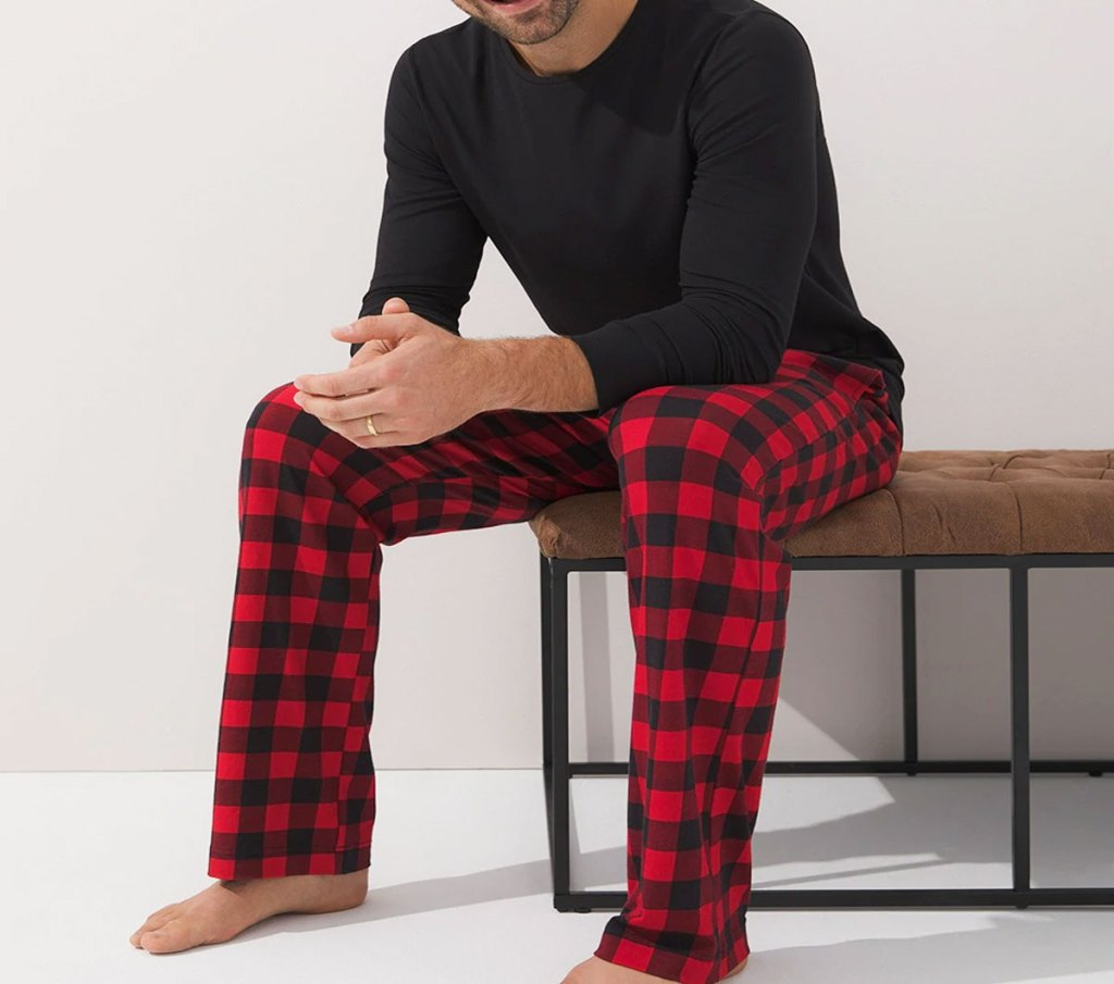 man sitting on a bench wearing a black long sleeve shirt and red and black buffalo plaid pajama pants