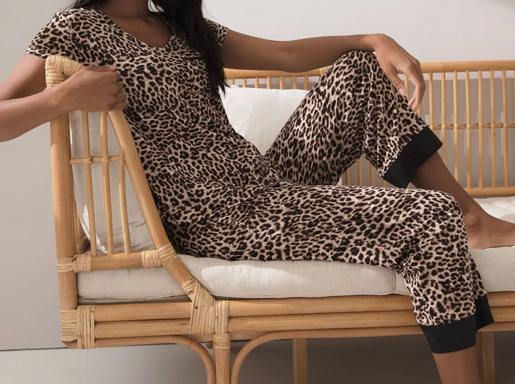 woman on wicker couch wearing matching set of leopard pajamas