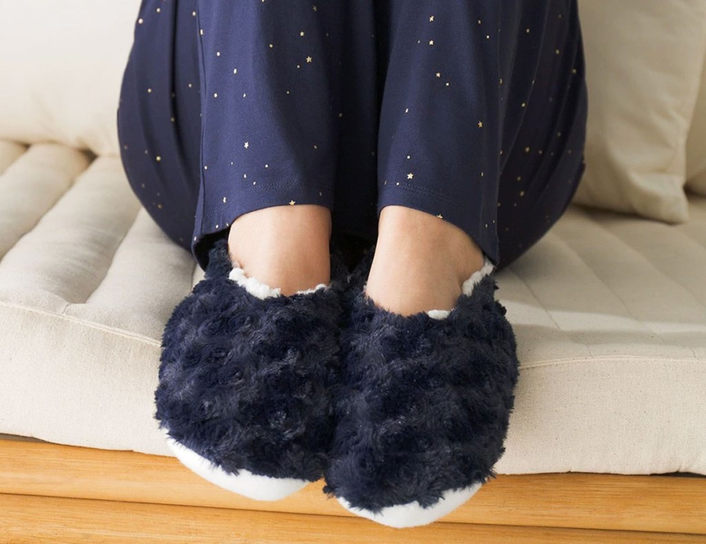 woman in navy blue fuzzy slipper socks and navy blue pajama pants