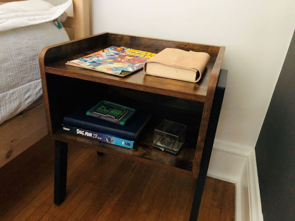 nightstand by a bed with books on it