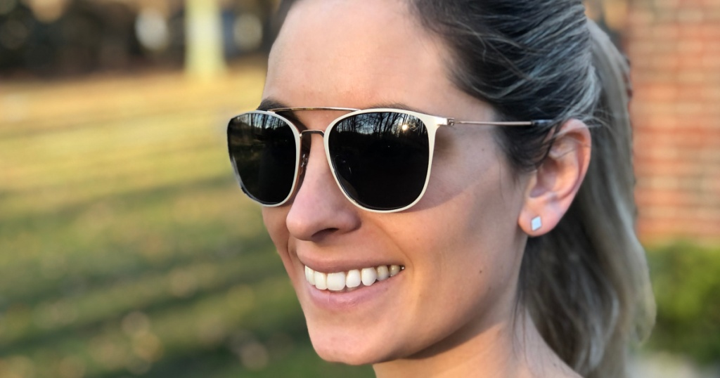 smiling woman standing outside wearing Sperry sunglasses