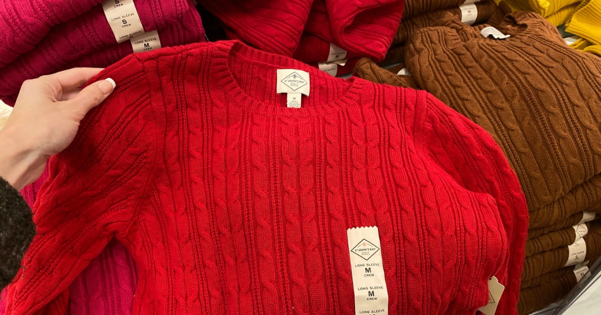 Hand holding up shoulder of St. John's Bay Women's sweater in red
