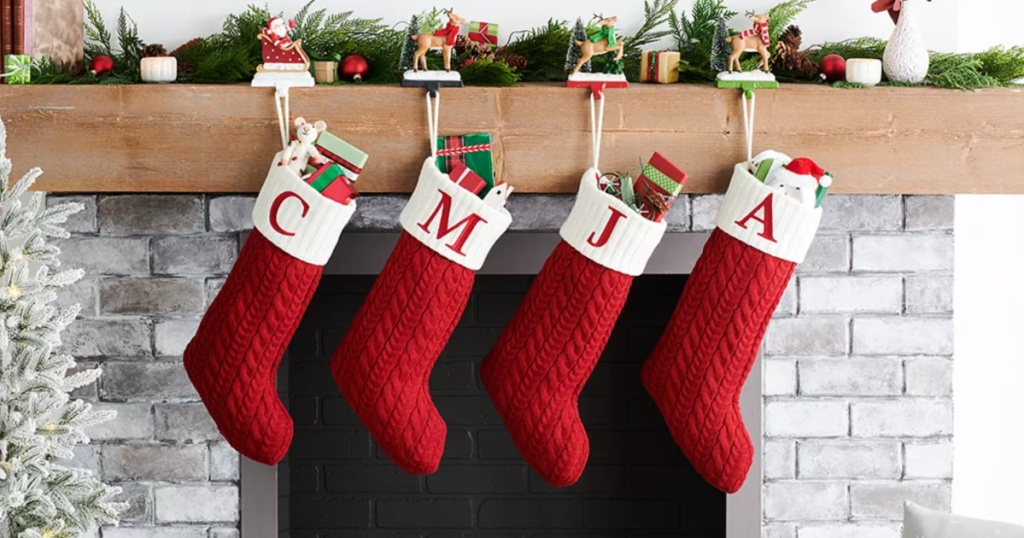 red and white monogrammed stockings hangng on a fireplace mantle