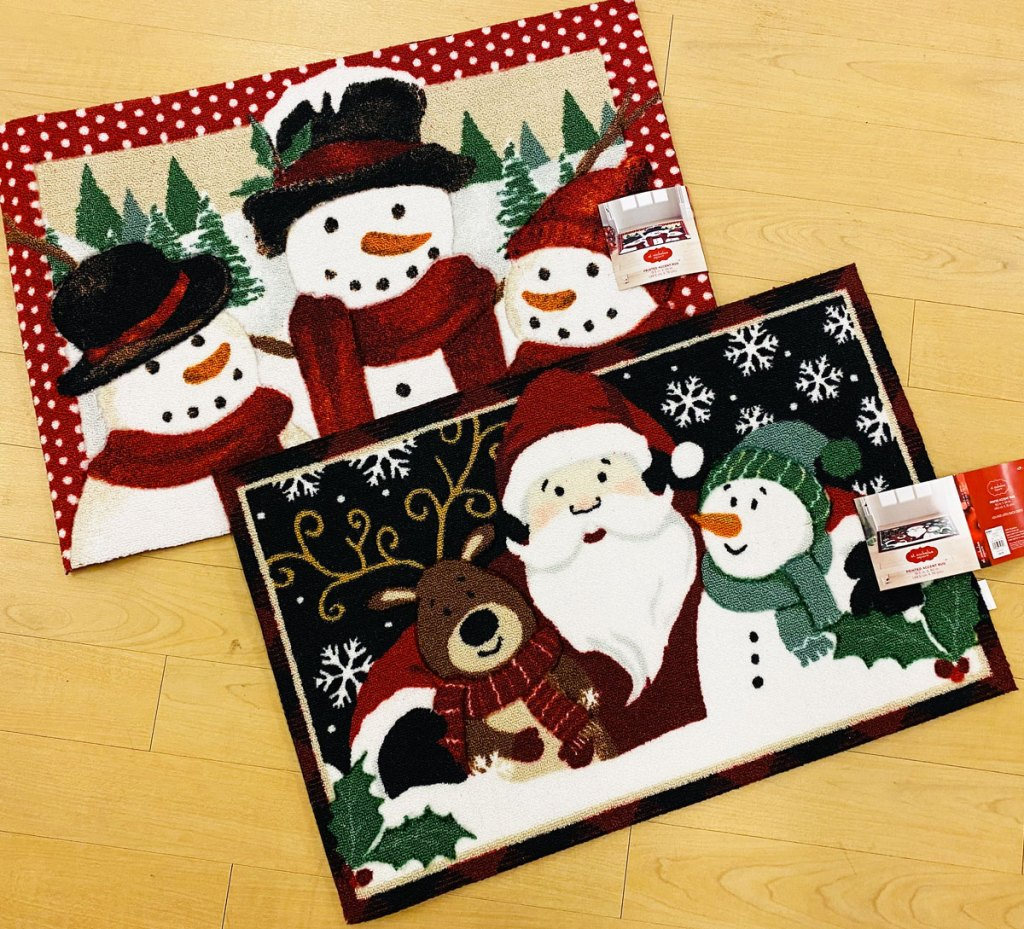 two snowmen themed doormats on a wood floor at kohl's