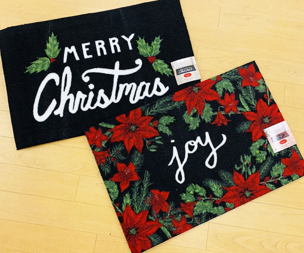two holiday accent rugs that say merry christmas and joy on them