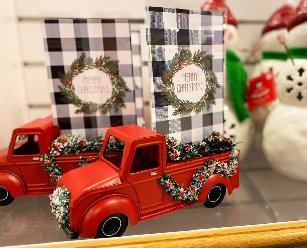 red trucks with photo frame in bed decorated with christmas greenery
