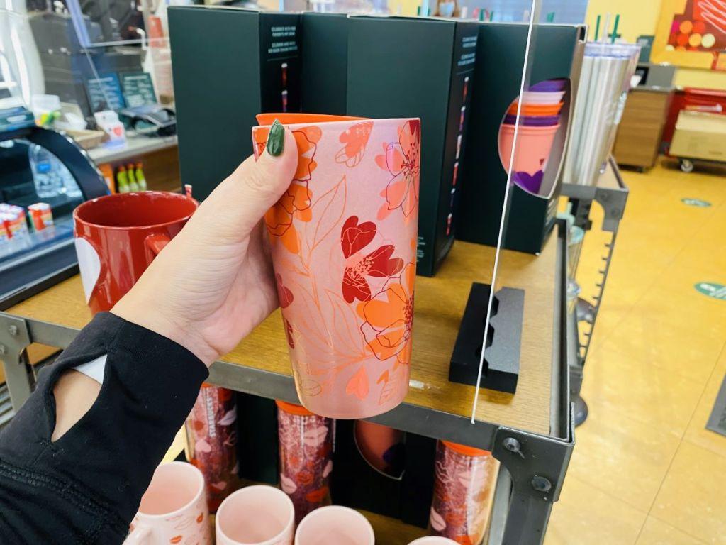 hand holding a Starbucks Floral Hearts Mug