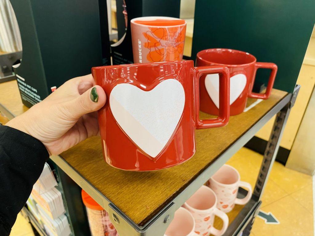 hand holding a Starbucks Heart Mug