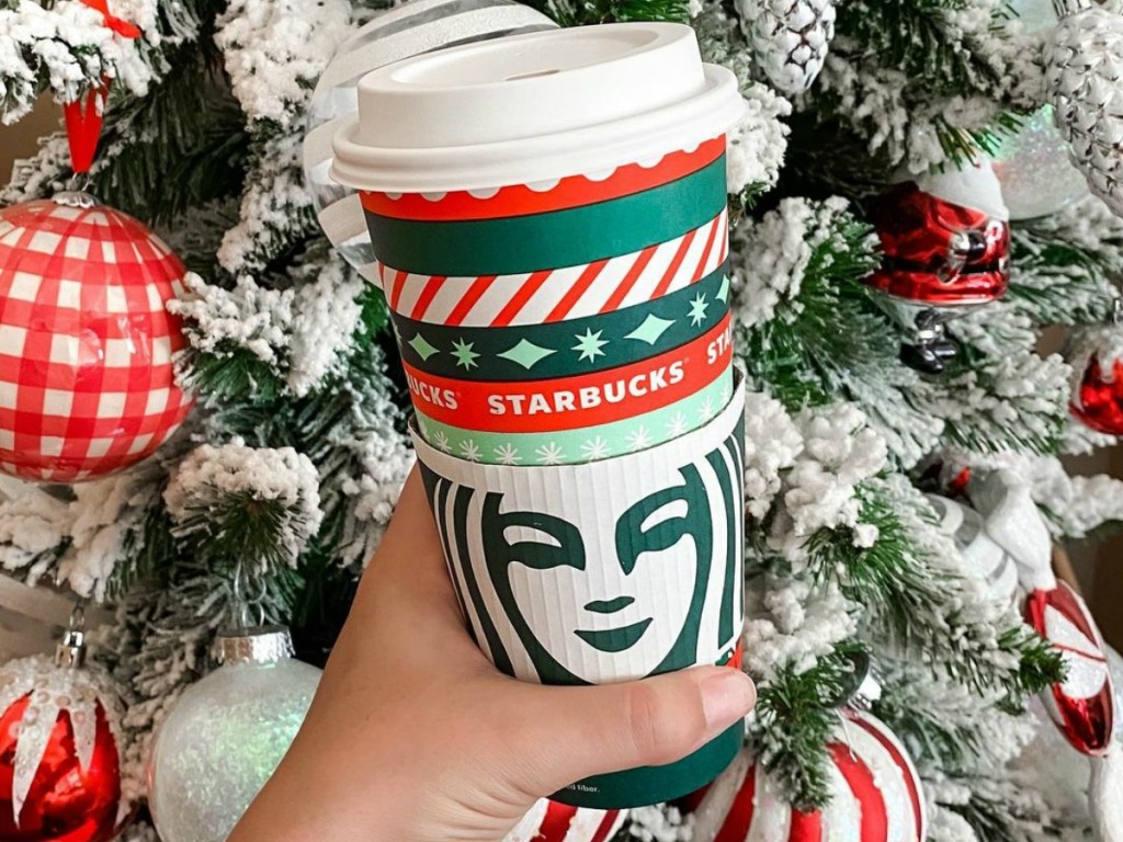 person holding Starbucks cup in front of flocked Christmas Tree